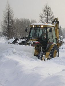 Caterpillar backhoe clearing snow